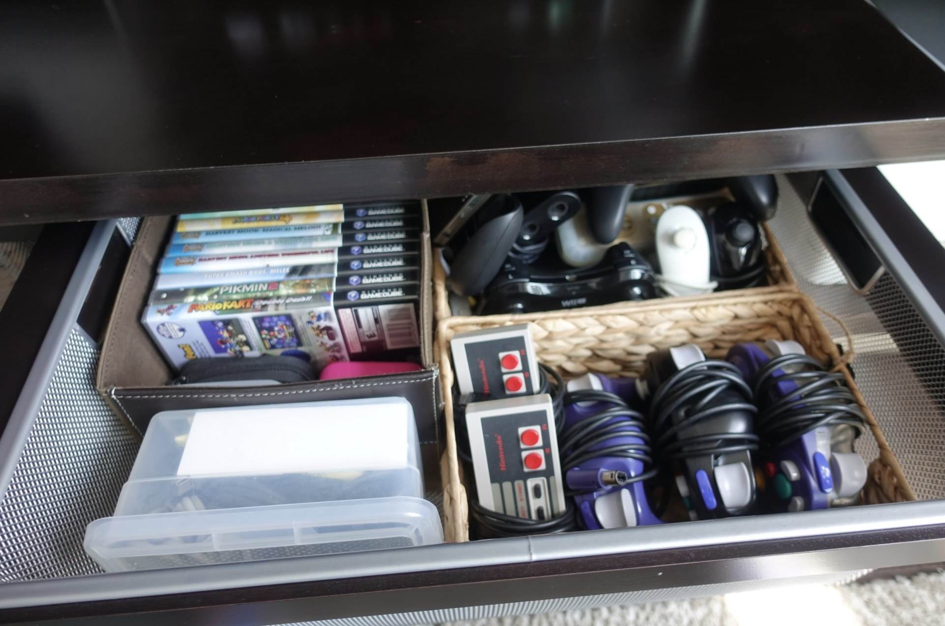 A drawer of video games and video game controllers