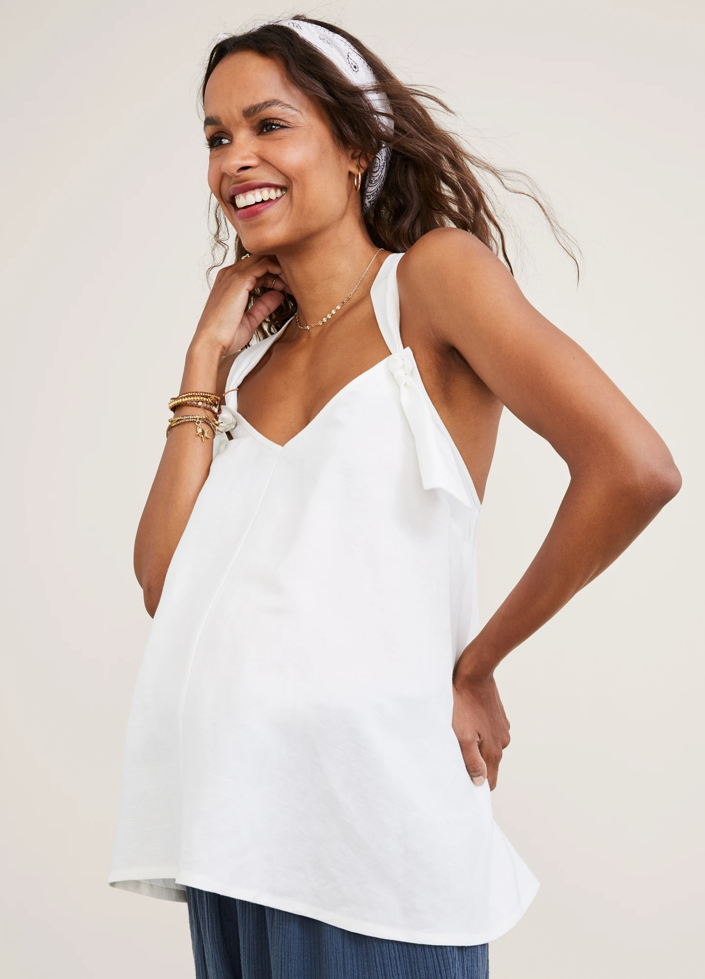 Third-trimester model wearing a white tank top