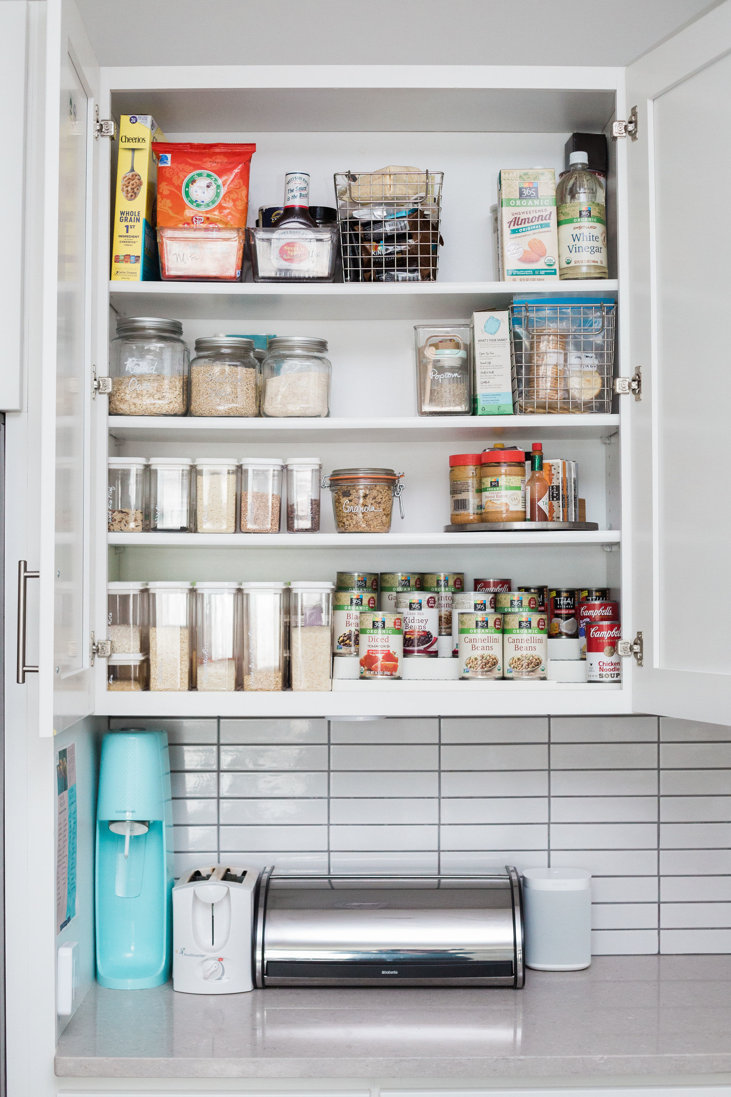 An open cabinet displaying plastic containers and jars filled with staples, a collection of cans on a step shelf, and condiments on a turntable above a Soda Stream, a toaster, a bread saver, and a speaker
