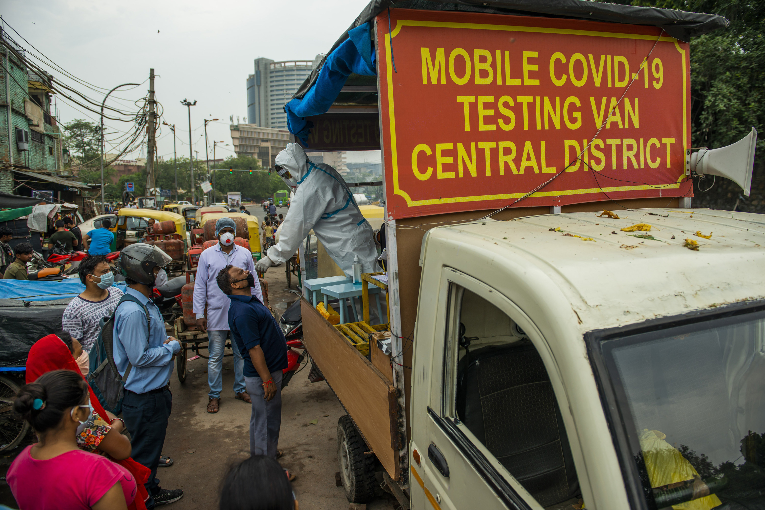 "A man stands in the bed of a pickup truck that reads ""Mobile COVID-19 Testing Van Central District,"" while administering a nasal swab"
