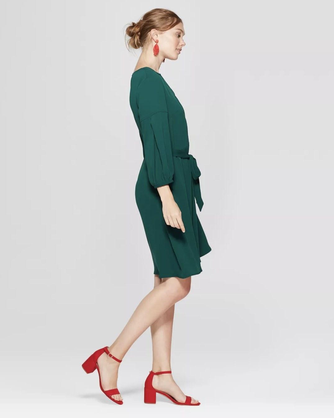 Model wears red heels with green dress.