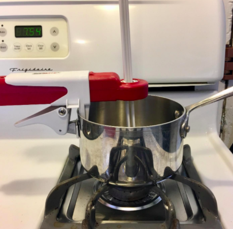 Reviewer uses red and white pot stirrer on top of a silver pot