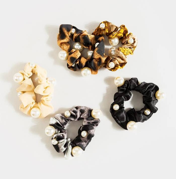 five scrunchies in different patterns with pearls on them