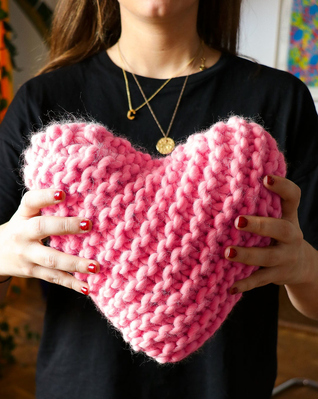 model holding small bright pink chunky knit pillow