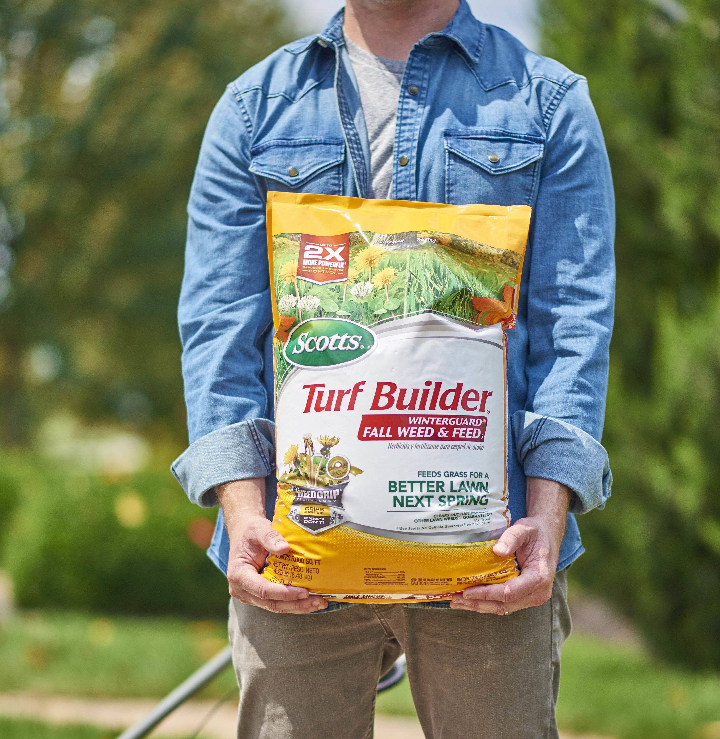 Model holding a large yellow bag of Scotts turf builder