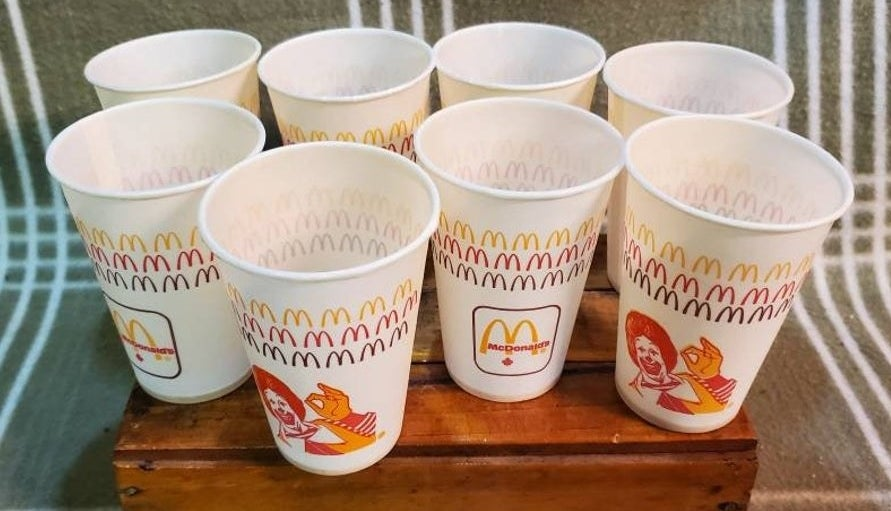 "McDonald's wax cups with an illustration of Ronald McDonald on giving an ""a ok"" hand sign on it."