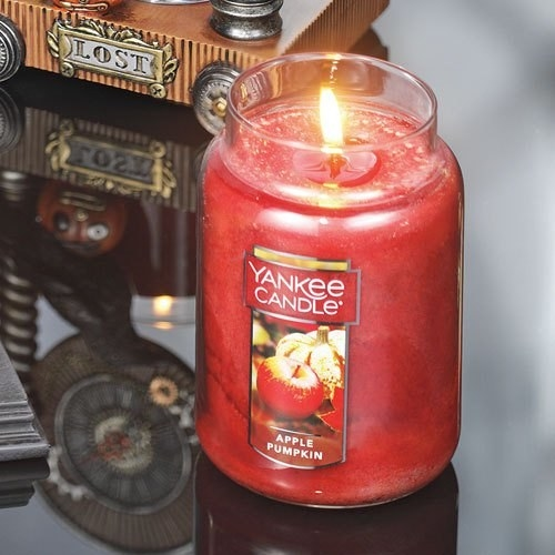 A glass jar with a lit red candle inside