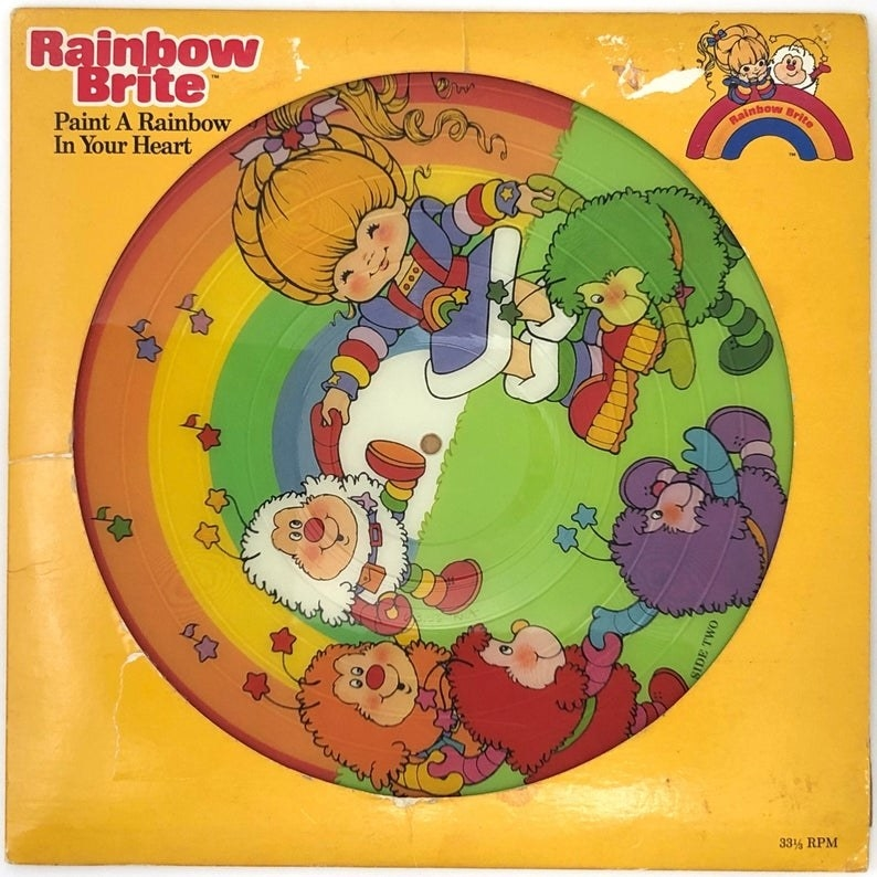 A Rainbow Brite picture disc which features Rainbow Brite dancing with Sprites and a large rainbow behind them.
