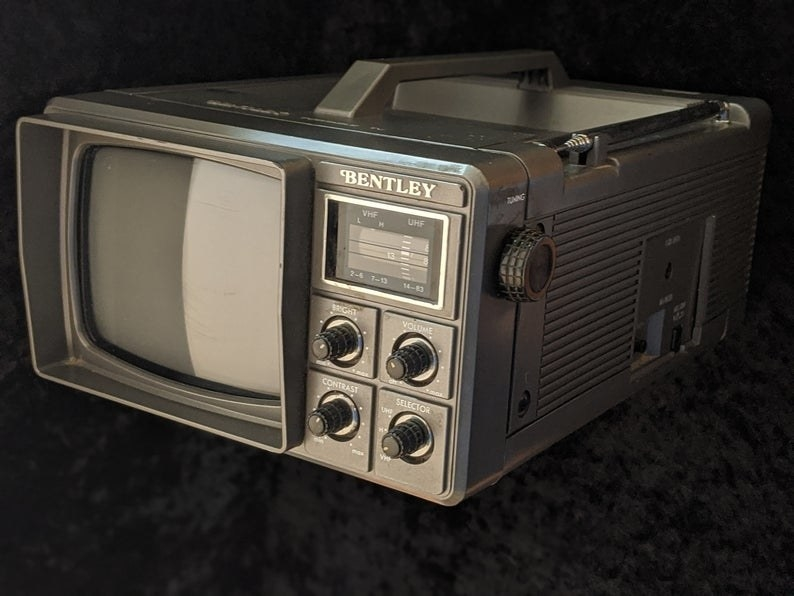A Bentley portable TV, which has a handle at top, a small screen with various knows next to it.
