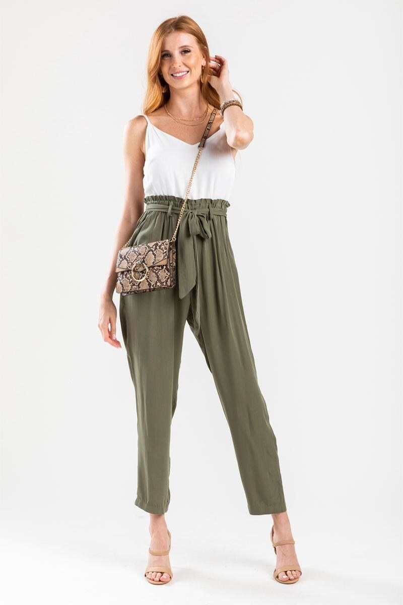 a model in a jumpsuit with olive green paperbag pants and a white spaghetti strap tank
