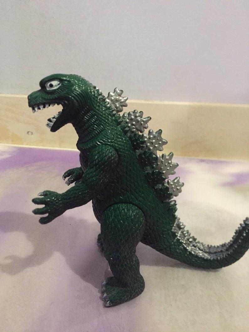 A green Godzilla posable toy.