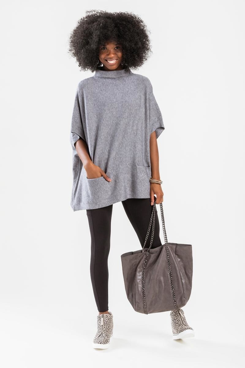 a model in the grey short-sleeved poncho