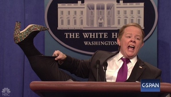 Melissa McCarthy as Sean Spicer, lifting her leg to show off a shoe