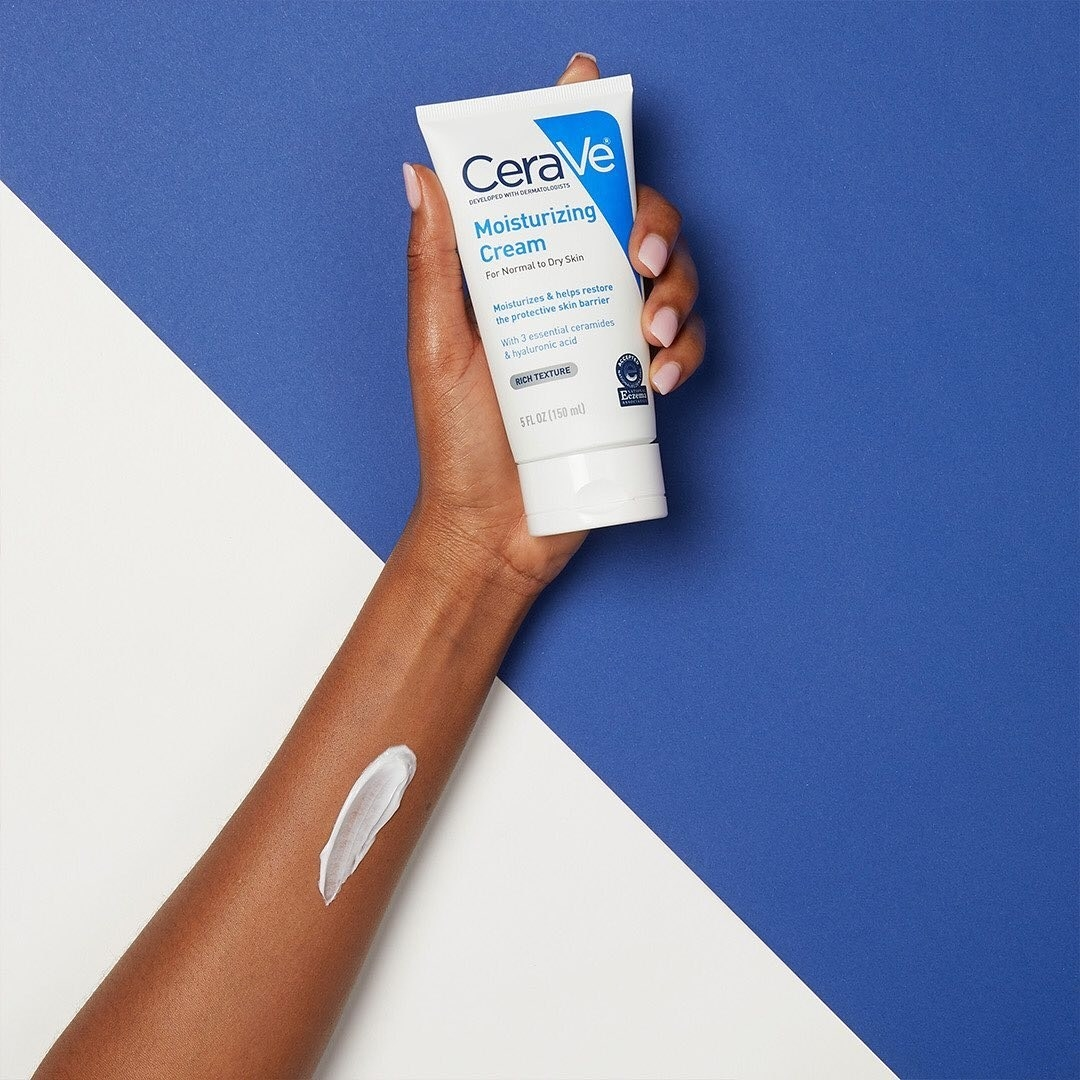A person holding up a tube of CeraVe moisturizing cream with a swatch on their wrist