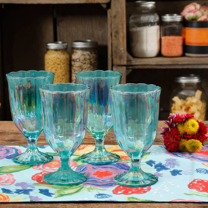 set of four green goblets on a table