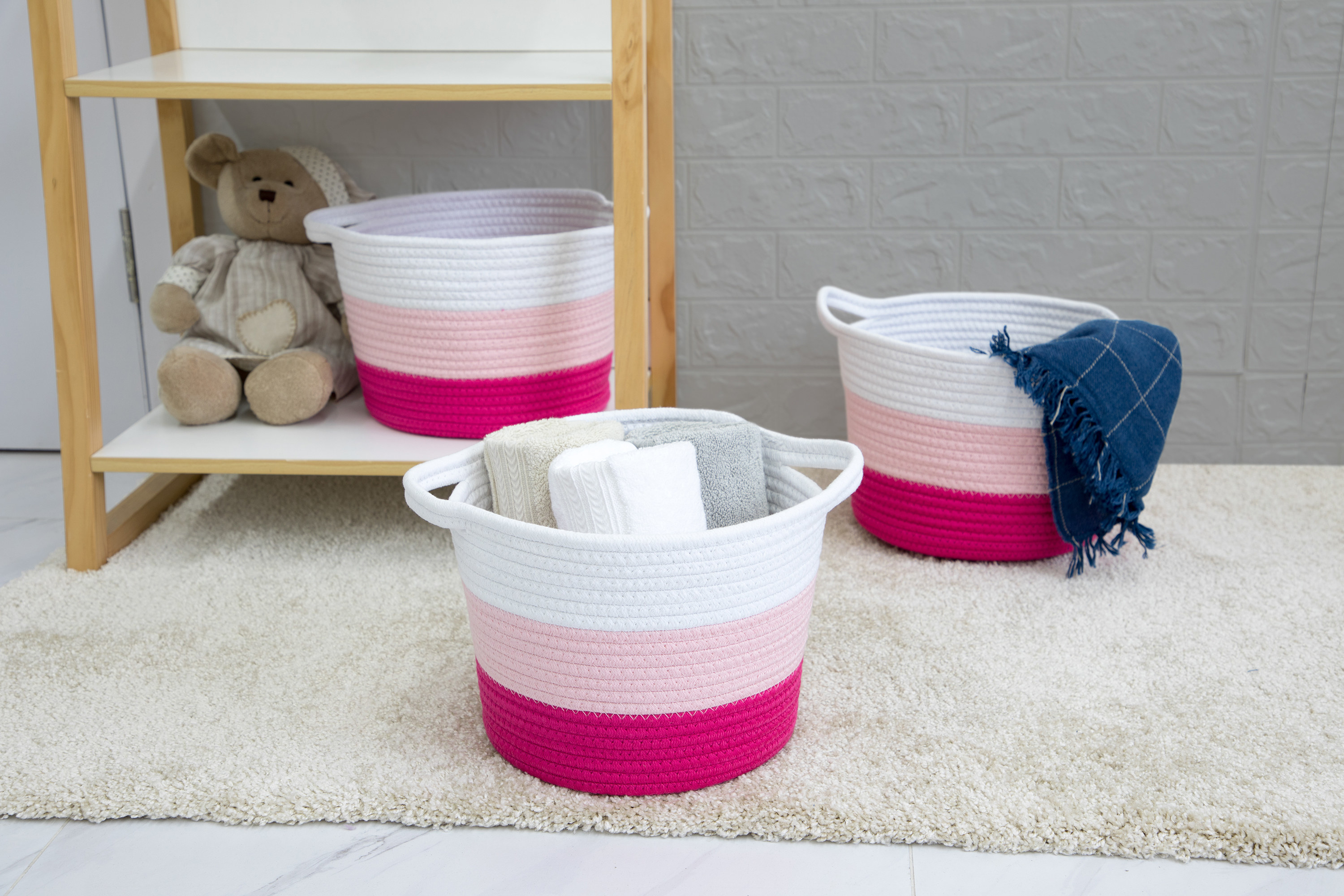 three pink storage baskets in children's room