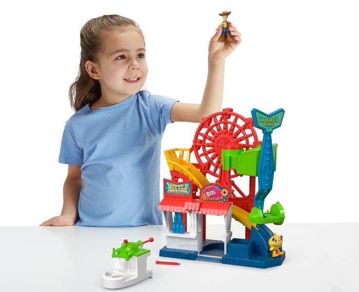 girl playing with toy story carnival set