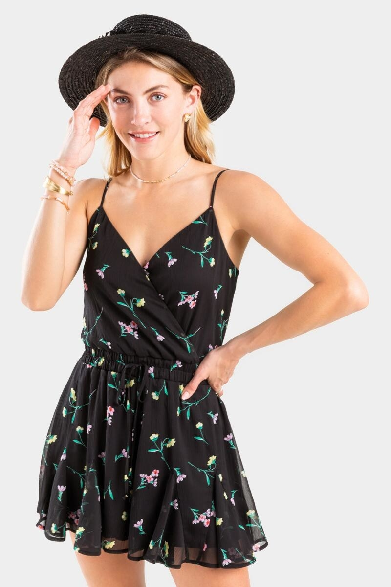 a model in the black romper with tiny florals all over it