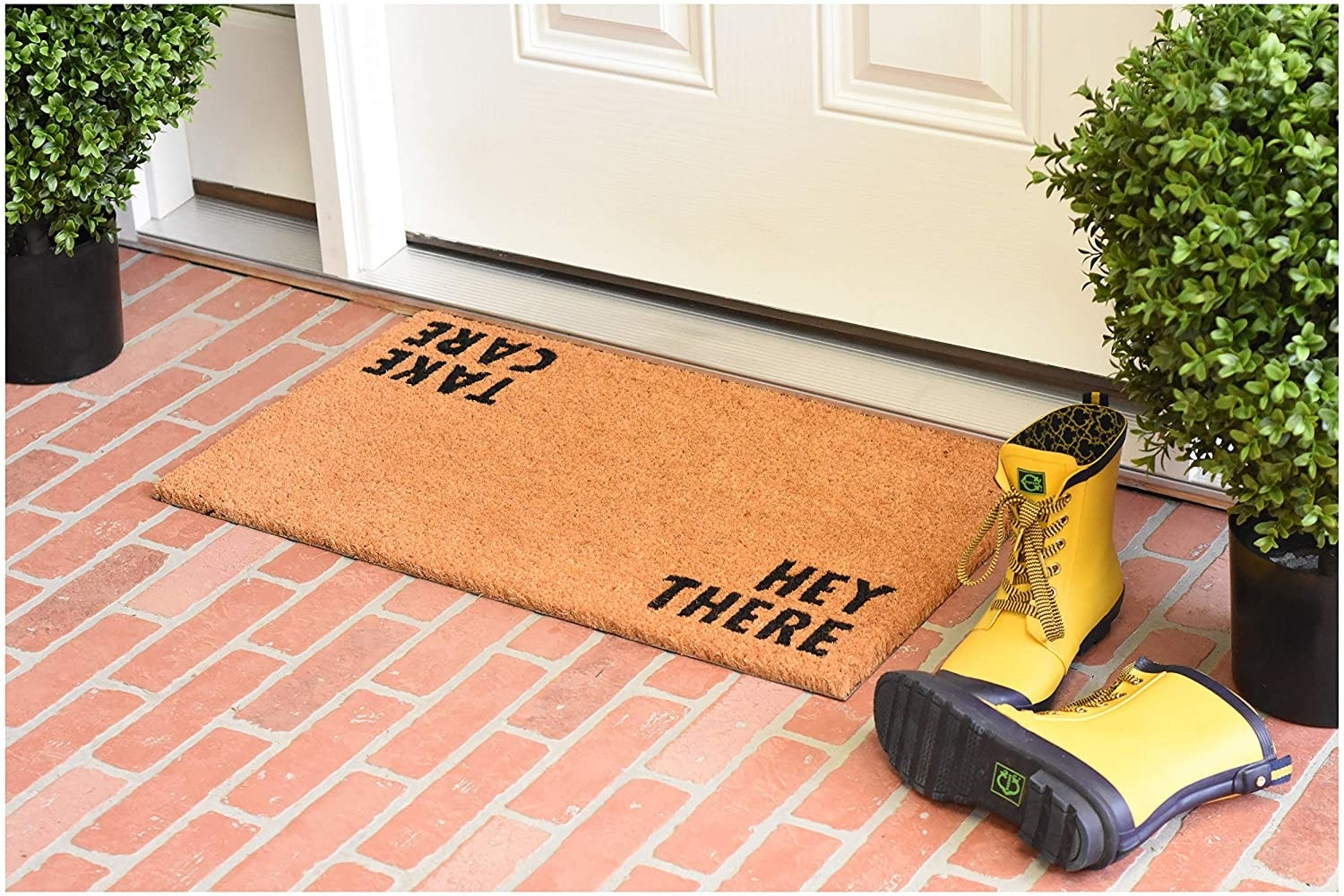 """exterior door with natural color welcome mat that says """"hey there"""" when entering the house, """"take care"""" when leaving"""