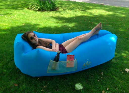 Reviewer lays down in blue inflatable lounger in their backyard