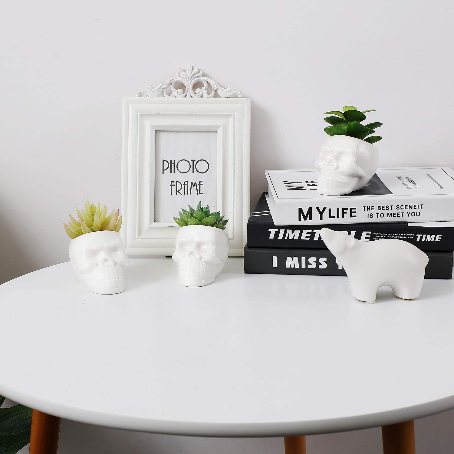 Three skull-shaped plant pots on a table with succulents inside of them