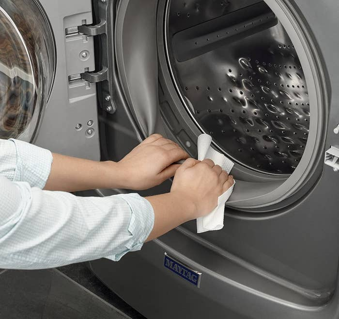 A person cleaning the rubber gasket of their washing machine with one of the wipes