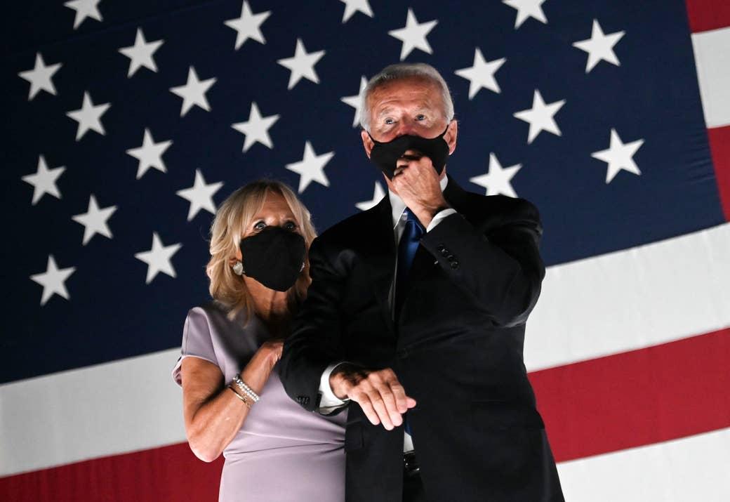 Joe and Jill Biden wear face masks, standing in front of an American flag