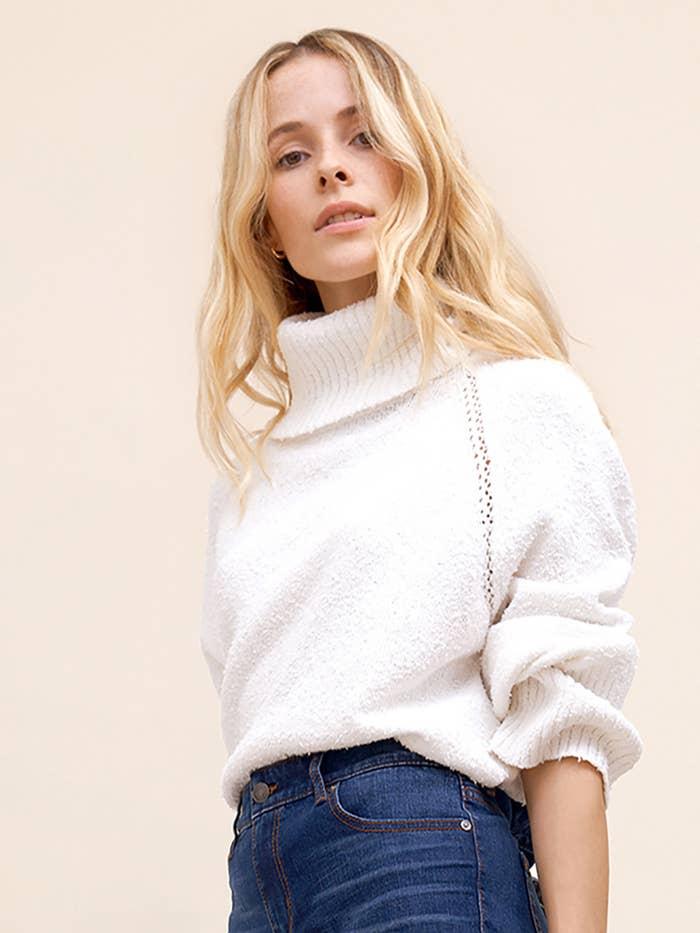 Model in white turtleneck sweater.