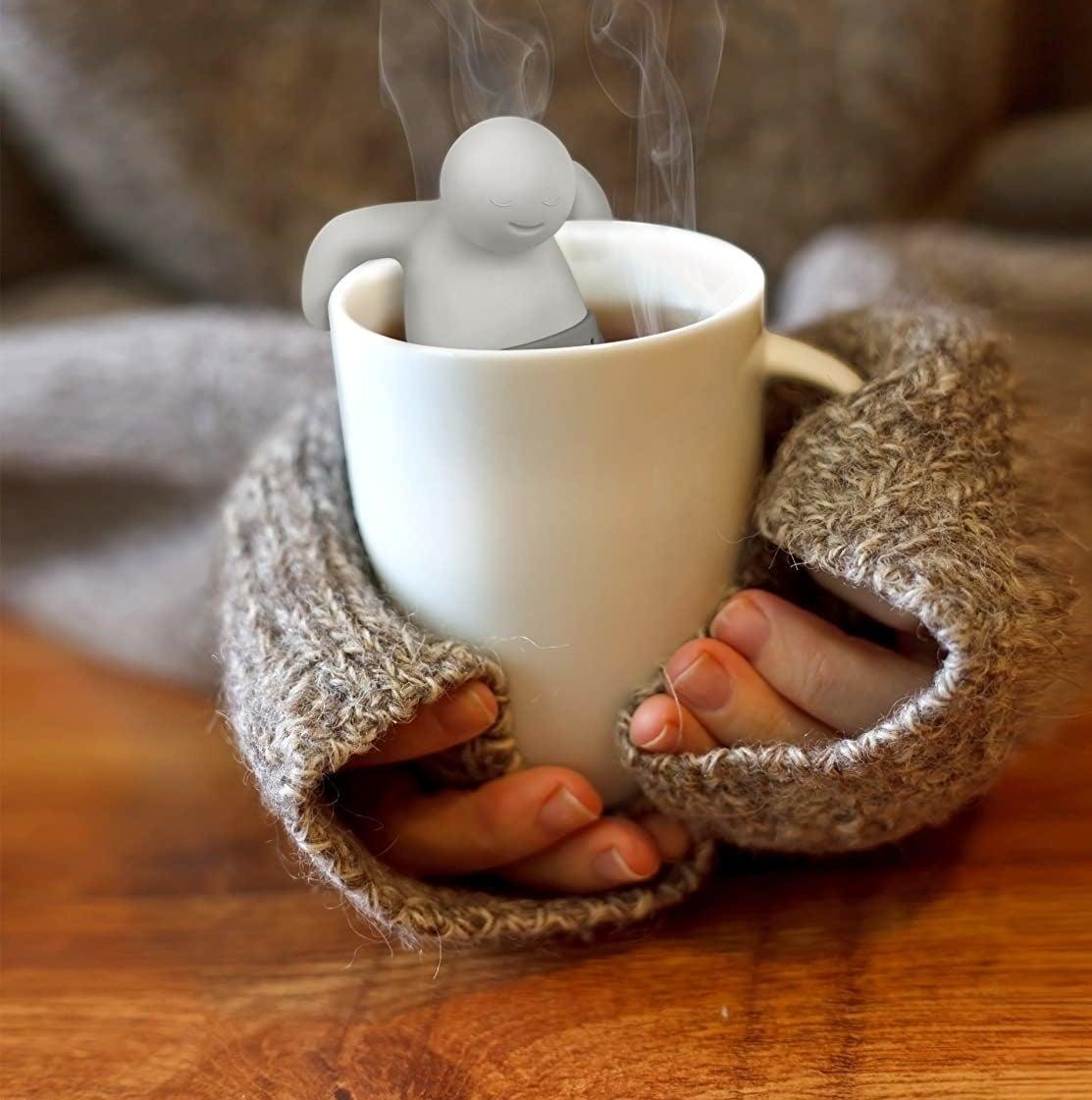 model holding mug with white tea infuser inside