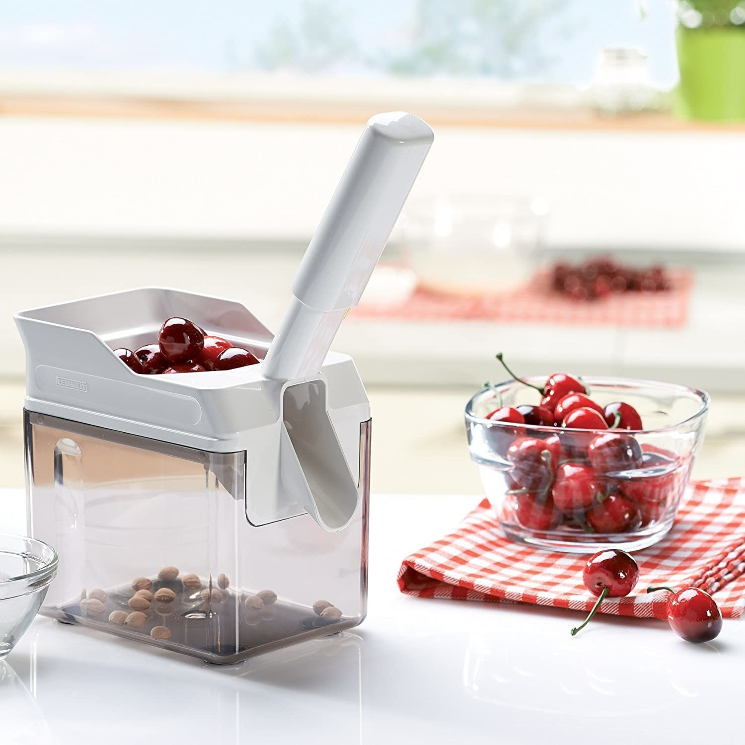 The cherry pitting machine on a kitchen counter next to a bowl of cherries