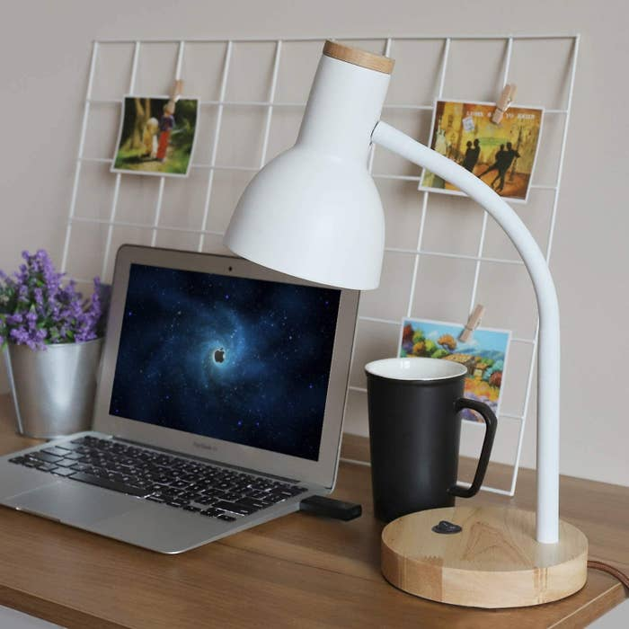 White desk lamp with wood on the end of the head and a wood base with an on-and-off switch