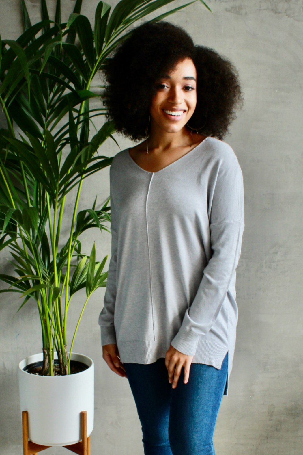 Model wearing the v-neck grey sweater with a seam down the front middle