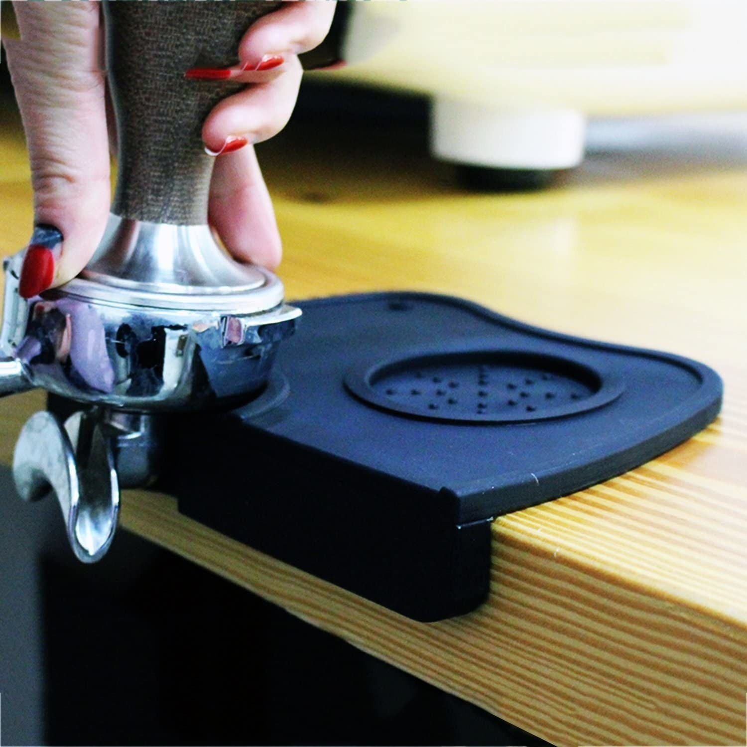 A person tamps an espresso container on the silicone mat
