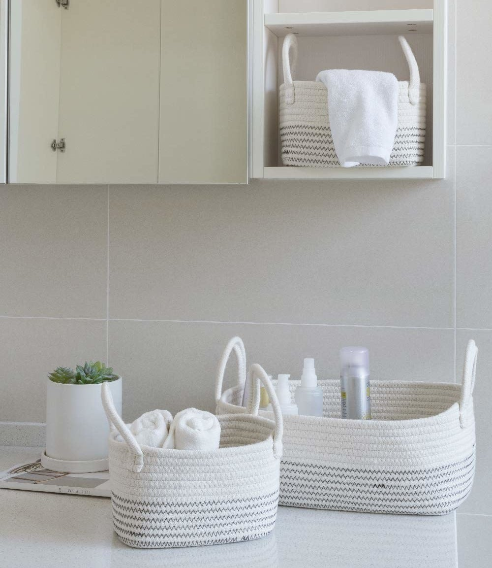 Three differently-sized woven baskets in white with grey zig-zag stripes around the bottom halves