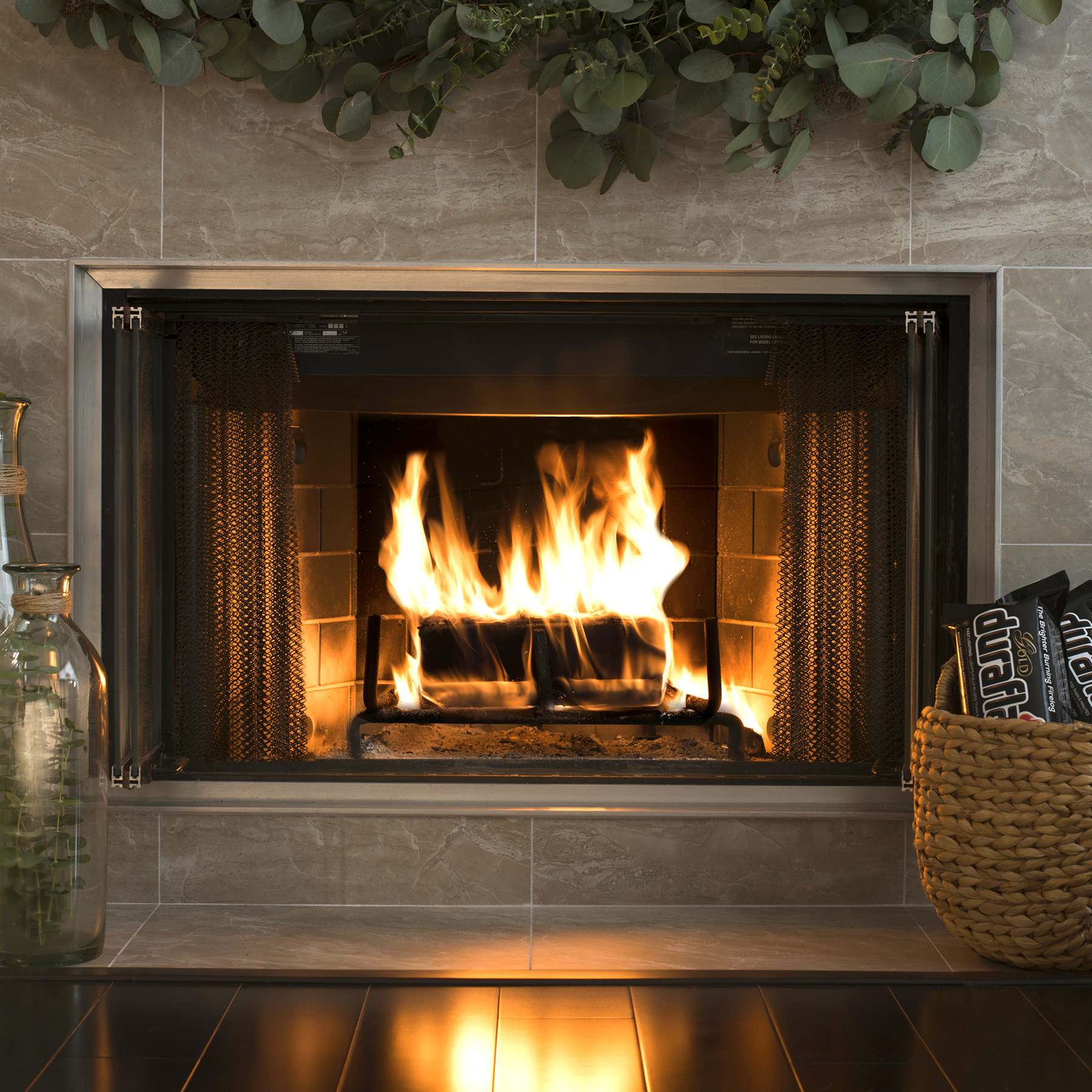 Packs of Duraflame logs next to a roaring fire