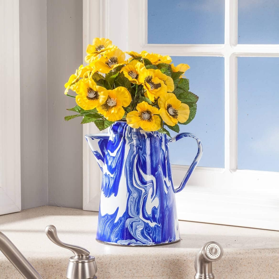 Tall enamel coffee pot with a blue and white marble-like pattern and flowers in it