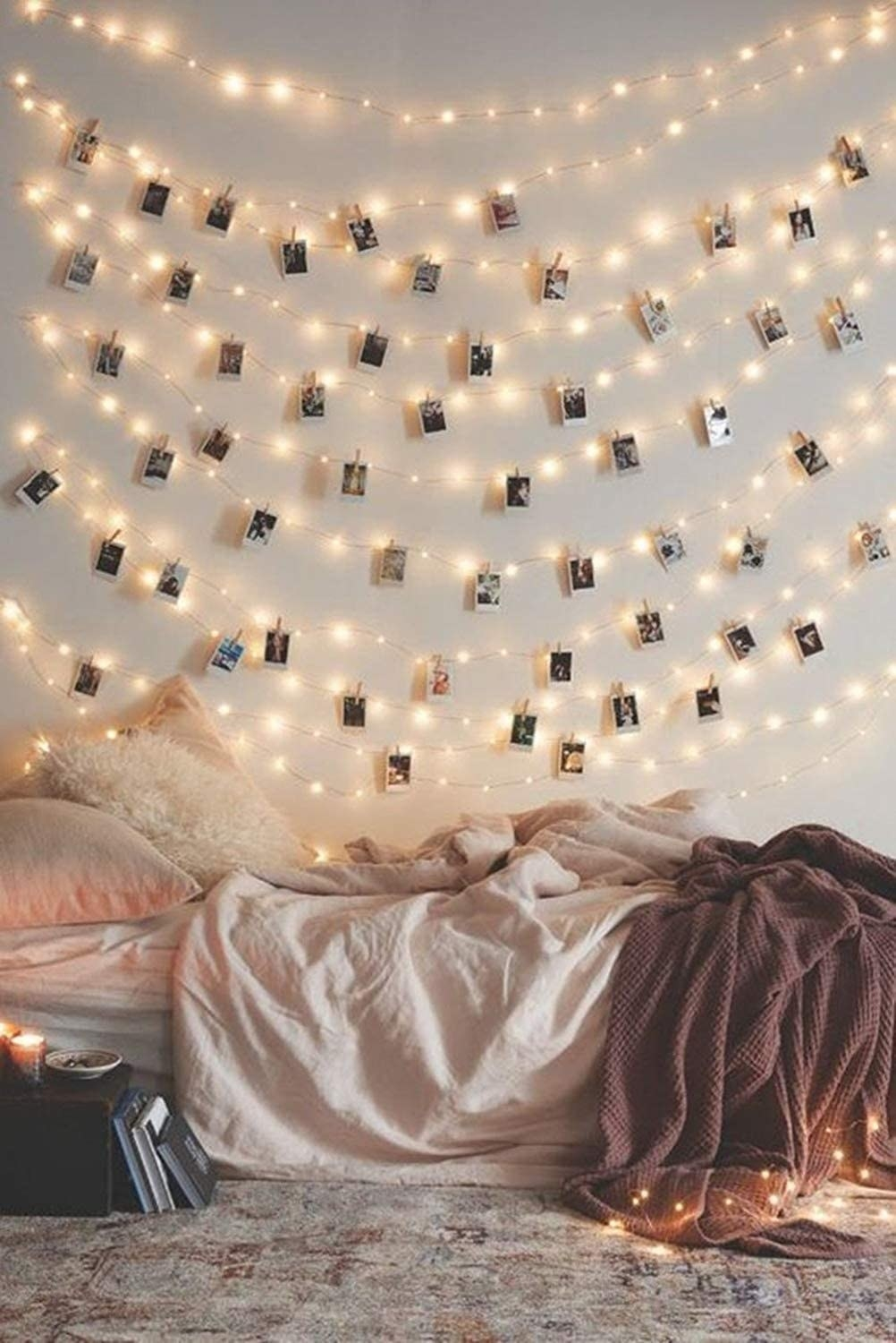 string lights with polaroid pics clipped onto them above a bed