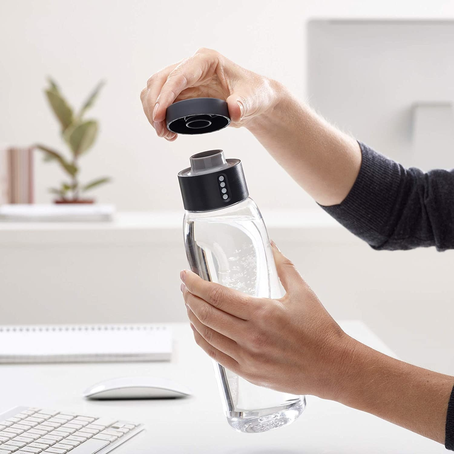 model holding clear water bottle with black cap