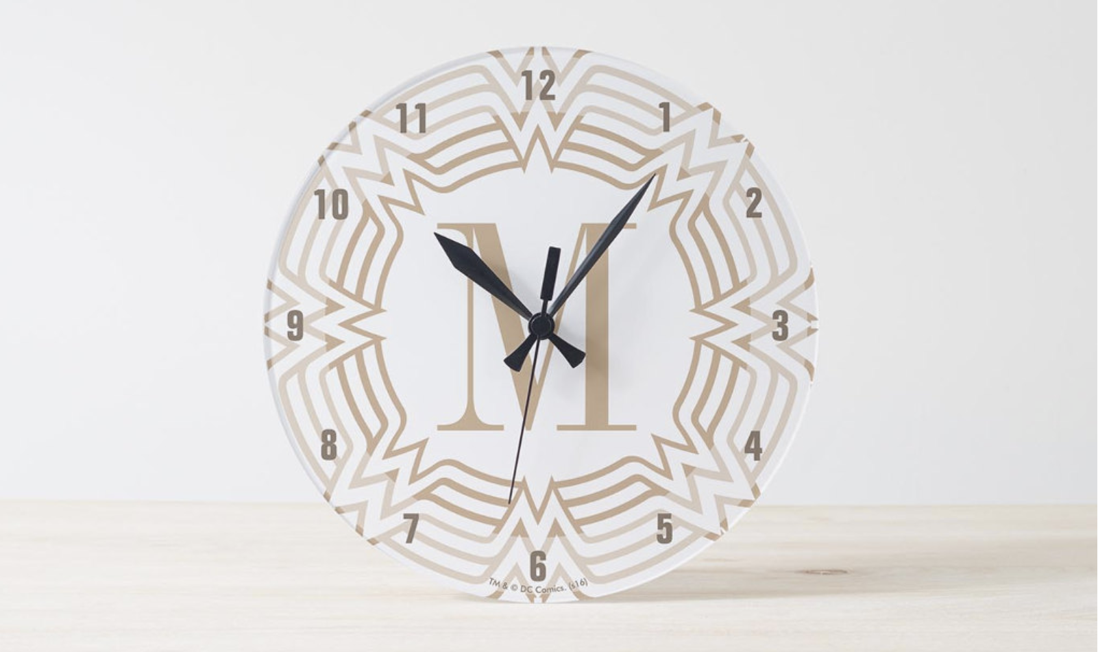 "A clear wall clock with an ""M"" at the middle"