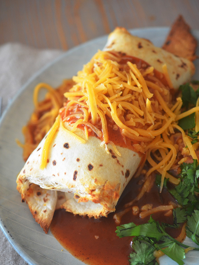 An air fried burrito with a golden brown tortilla covered in red enchilada sauce and shredded cheddar cheese.