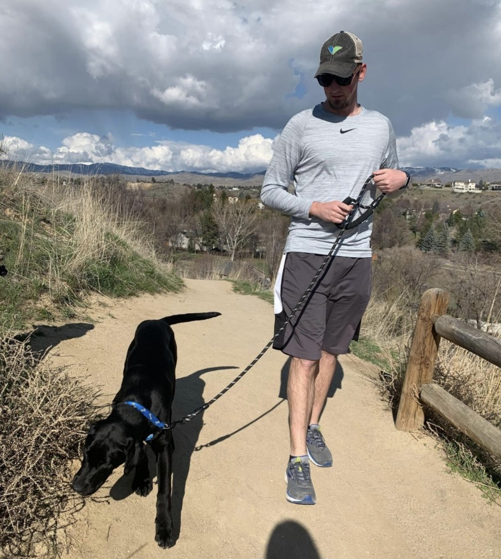 A man walking a black lab on a trail with a leash