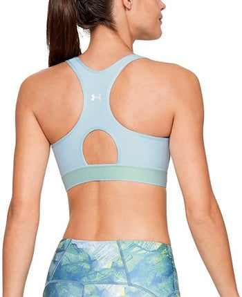 a model showing the keyhole cut out in the back of the sports bra in light blue