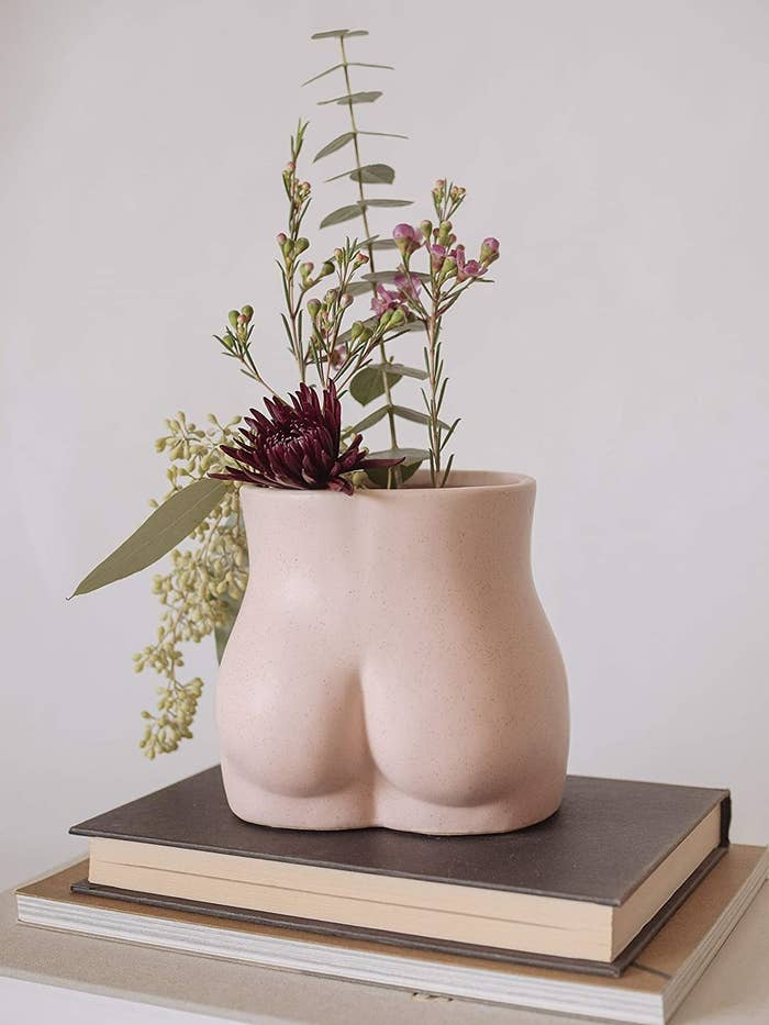A vase that's shaped like a butt in light pink with a wide open top with flowers in it