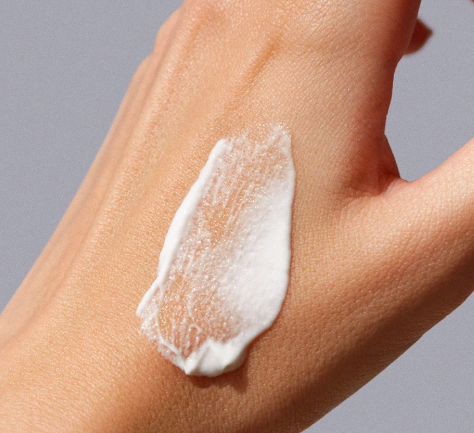 A model's hand showing the texture of the cream