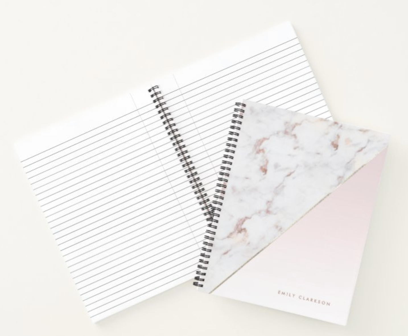Two notebooks, one with a pink and marble cover and one opened to show the line spacing
