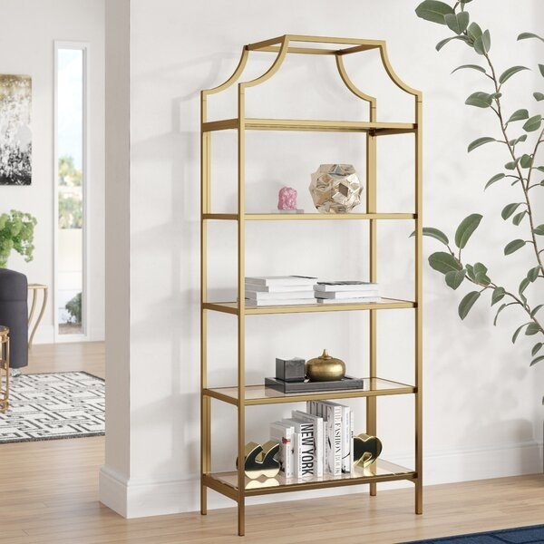 Gold colored metal frame with five glass top shelves and canopy top