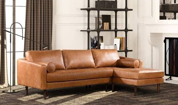 Mid century modern sofa in tan leather with two round arm rest pillows. Sits three with sectional.