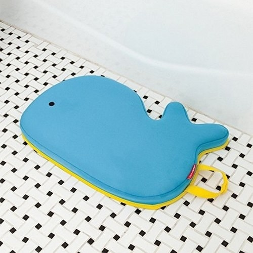 a blue whale-shaped kneeling pad near a bath tub