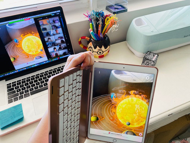 An image of a rendering of the solar system broadcasted on an iPad to a digital classroom