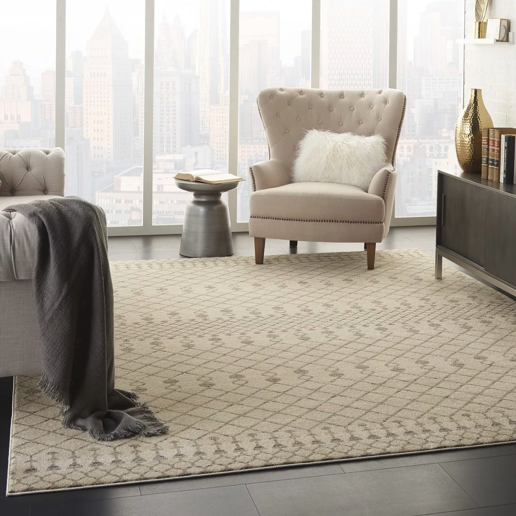 An off-white area rug with a gray Morrocan tribal pattern under a gray couch, a beige armchair, and a dark brown console